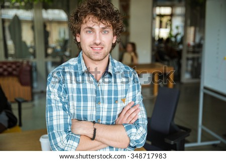 Portrait of handsome attractive cheerful young curly man in plaid shirt with arms crossed in office - stock photo