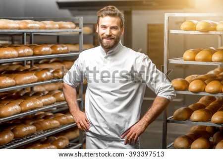 Portrait of handsome baker at the bakery with breads and oven on the background - stock photo