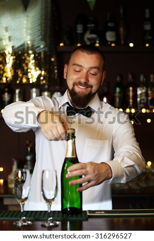 Portrait of handsome bartender with champagne bottle - stock photo