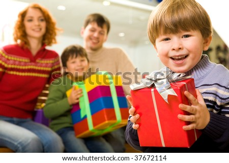 Portrait of handsome boy with giftbox on background of his parents and brother - stock photo