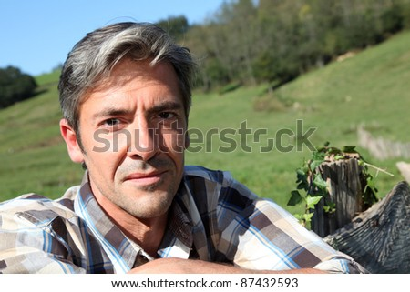 Portrait of handsome breeder leaning on fence - stock photo