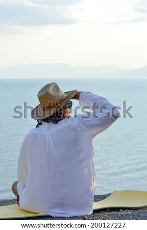 portrait of handsome brunette young man in white shirt cool hat & sun glasses having fun relaxing sitting on the sea or ocean beach & looking into the distance on light blue sky copy space background - stock photo