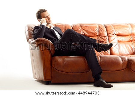 Portrait of handsome businessman in suit talking phone sitting on the couch isolated on white - stock photo