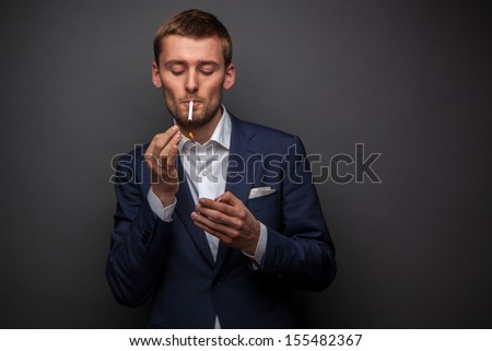 portrait of handsome businessman with cigarette on black - stock photo