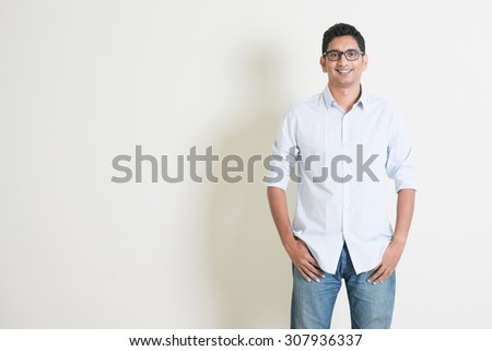 Portrait of handsome casual business Indian guy smiling, hands in pocket, standing on plain background with shadow, copy space at side. - stock photo