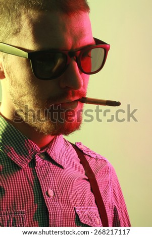 Portrait of handsome casual stylish young man with sunglasses, plaid short sleeve shirt and braces smoking cigarette with holder in green and red colored lights - stock photo