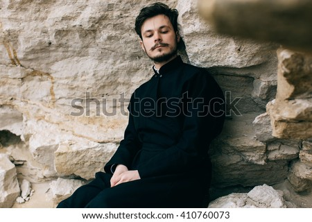 Portrait of handsome catholic bearded priest or pastor posing outdoors in mountains - stock photo