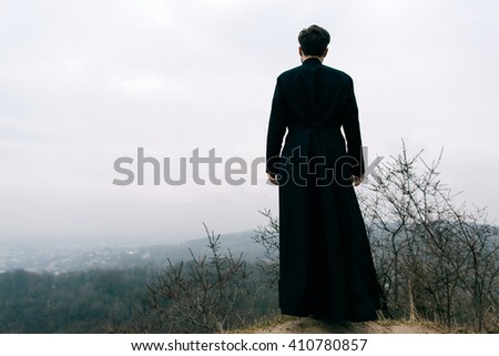 Portrait of handsome catholic bearded priest or pastor posing outdoors in mountains. City.  - stock photo