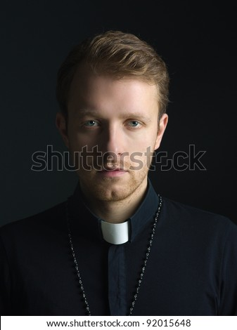 Portrait of handsome catholic priest or pastor with dog collar, black background. - stock photo