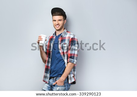 Portrait of handsome caucasian man standing on grey background. Young man with shirt and cap looking at camera and holding coffee to go - stock photo