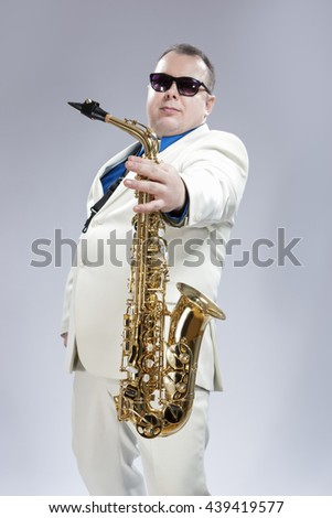 Portrait of Handsome Caucasian Saxophone Player With Music Instrument in Front. Posing Against White. Vertical Image - stock photo