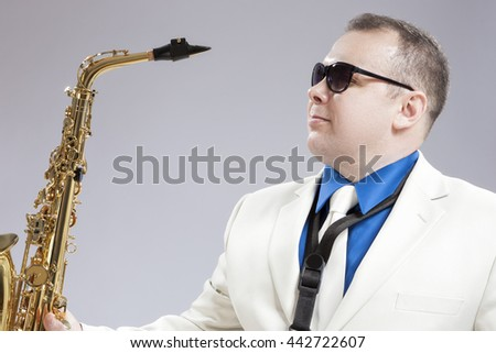 Portrait of Handsome Caucasian Saxophone Player With Music Instrument in Front. Posing Against White. Horizontal Image Composition - stock photo