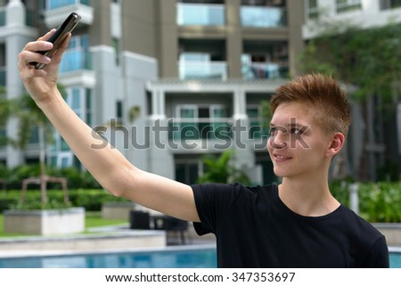 Portrait of handsome Caucasian teenager boy standing outdoors and taking selfie picture with mobile phone - stock photo