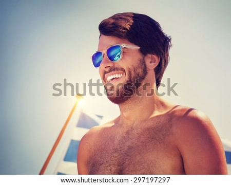 Portrait of handsome cheerful man over blue sky background, traveling on water transport with the Greek flag on board, happy beach holidays - stock photo