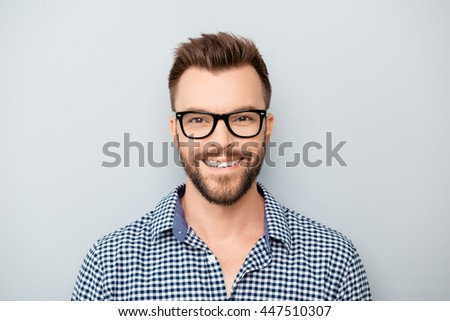 Portrait of handsome cheerful young smiling man in glasses - stock photo