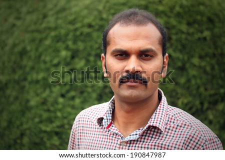 Portrait of handsome confident indian businessman with bald head standing against green background, with serious look. The photo is of a middle aged manager showing stress of management jobs - stock photo
