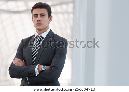 Portrait of handsome confident young businessman standing arms crossed, smiling happy, looking at camera. - stock photo