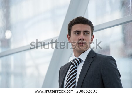 Portrait of handsome confident young businessman standing relaxed, smiling happy, looking away - stock photo