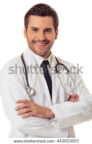 Portrait of handsome doctor in white coat looking at camera and smiling while standing with crossed arms, isolated on white background - stock photo
