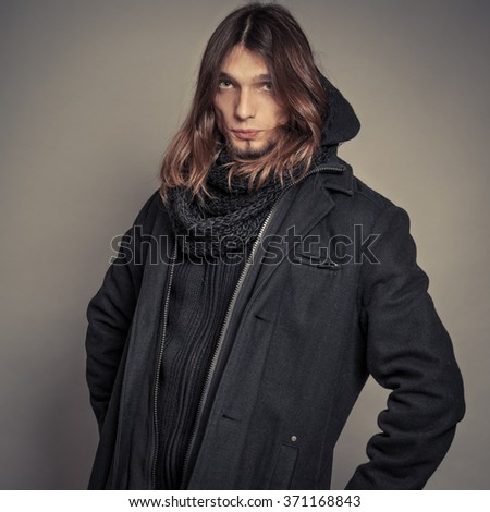 Portrait of handsome fashionable man wearing black coat and scarf. Young guy posing in studio. Winter or autumn fashion. Instagram filter. - stock photo