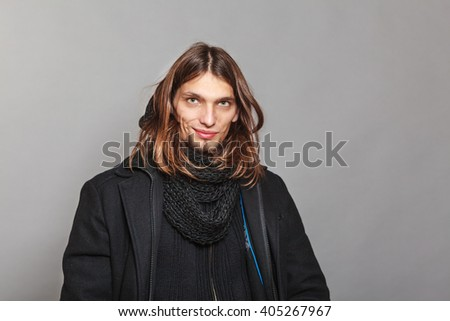 Portrait of handsome fashionable man wearing black coat and scarf. Young guy posing in studio. Winter or autumn fashion. - stock photo