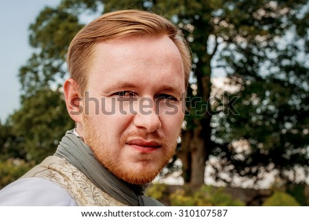 Portrait of handsome ginger hair man dressed in regency period costume. Image with selective focus - stock photo
