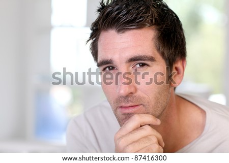 Portrait of handsome guy relaxing at home - stock photo