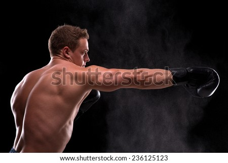 Portrait of handsome  happy  muscular  boxer  looking at camera on black background waist up with copy place  side view  - stock photo