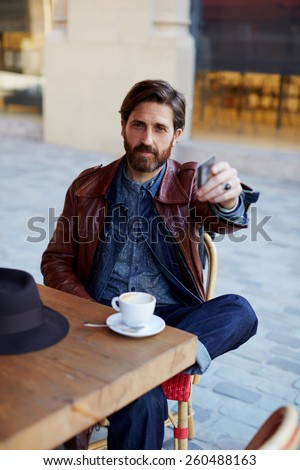 Portrait of handsome hipster man paying for his coffee with a credit card at the cafe, customer paying at a coffee shop with a credit card - stock photo