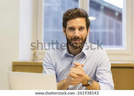 Portrait of handsome hipster style bearded man in office. Looking camera - stock photo