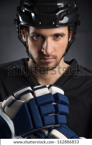 Portrait of handsome hockey player in black helmet. Isolated on black  - stock photo
