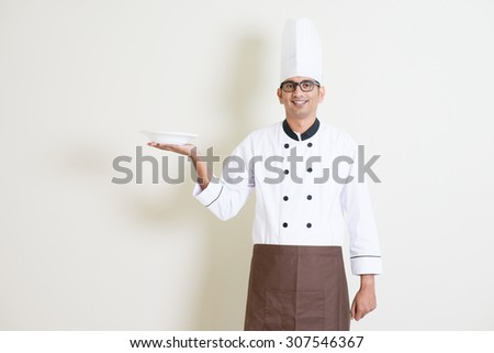 Portrait of handsome Indian male chef in uniform presenting an empty plate and smiling, standing on plain background with shadow, copy space. - stock photo