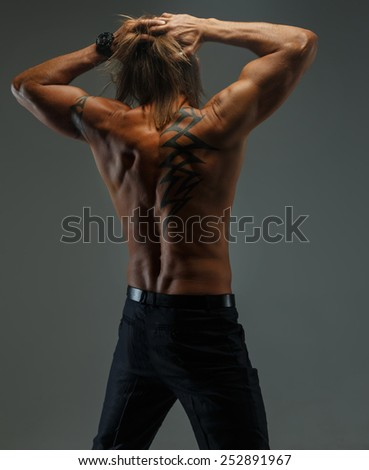Portrait of handsome long-haired man with naked torso. Isolated on gray background.  - stock photo