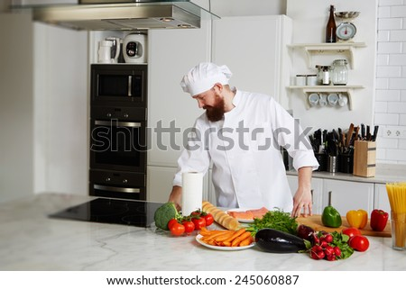 Portrait of handsome male chef in uniform prepare his kitchen for began to cook - stock photo