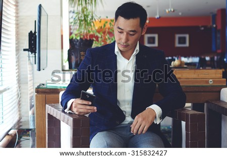 Portrait of handsome man dressed in luxury clothes chatting on his smart phone while sitting in cozy coffee shop inside, confident man entrepreneur using cell telephone while relaxing in cafe  - stock photo