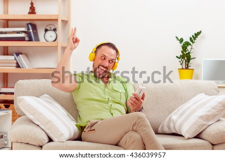 Portrait of handsome man happy listening to music at home while sitting on sofa or couch. Cheerful man spending his weekends at home. - stock photo