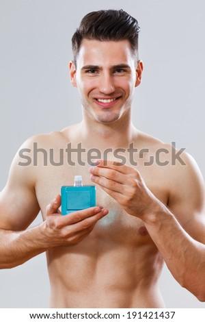 Portrait of handsome man holding aftershave,Skin care after shave - stock photo