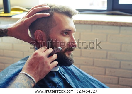 portrait of handsome man in barbershop. barber shaving man with straight razor  - stock photo
