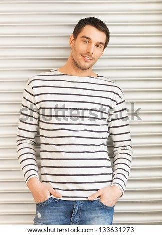 portrait of handsome man in casual clothes leaning to wall - stock photo