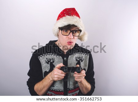 Portrait of handsome man in Christmas hat holding joystick for video games  - stock photo