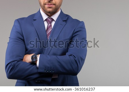 Portrait of handsome man in suit crossed arms confidently. He is standing and posing. Isolated and copy space in right side - stock photo