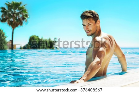 Portrait of handsome man in swimming pool - stock photo