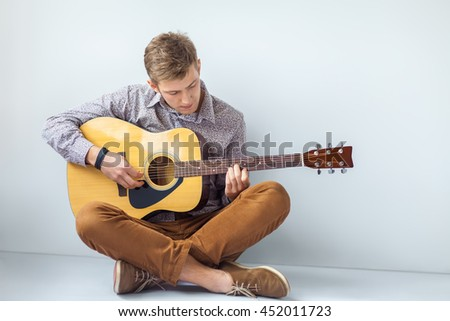 Portrait of handsome man playing guitar siting on floor with copy space - stock photo