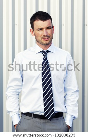 Portrait of handsome man posing with hands in pockets - stock photo