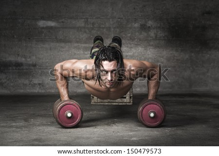 portrait of handsome man pushing up with weights - stock photo