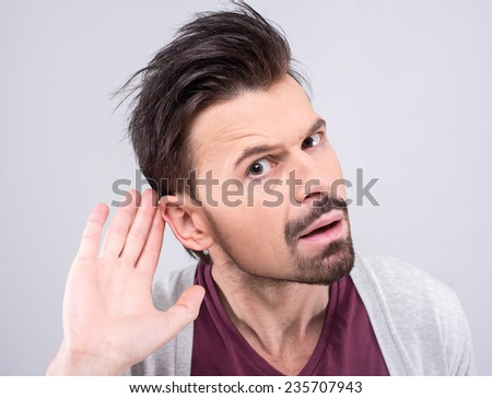 Portrait of handsome man secretly listening on private conversation. Human face, expression, emotion, body language. - stock photo