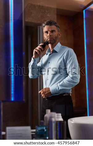 Portrait Of Handsome Man Shaving His Face, His Beard With Electric Razor While Standing In Modern Luxury Interior. Male Is Trimming His Facial Hair Indoors - stock photo
