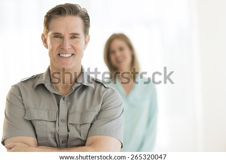 Portrait of handsome man smiling with woman standing in background at home - stock photo