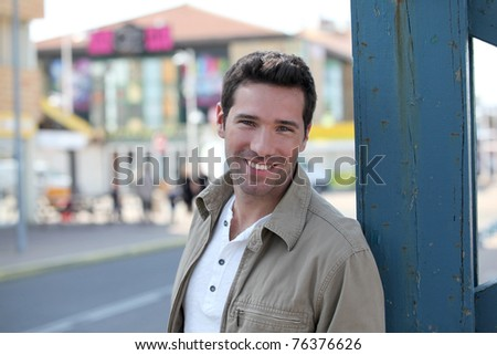Portrait of handsome man standing in town - stock photo