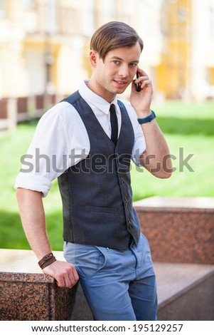 Portrait of handsome man talking on the cell phone, urban background  - stock photo